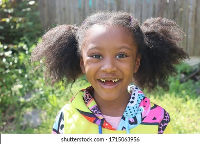 Happy African American girl missing two frount teeth smiling outdoors