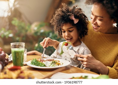 Happy African American girl sitting on mother's lap while she is feeding her at dining table.