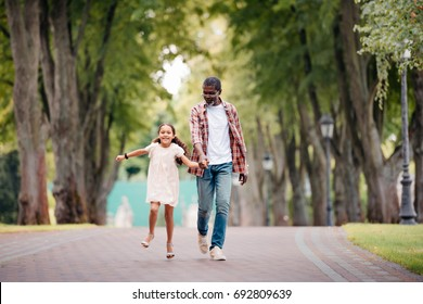 happy african american granddaughter holding hands with grandfather and walking in park