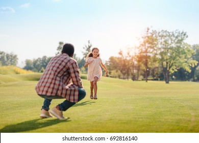 happy african american granddaughter running to grandfather on green lawn in park