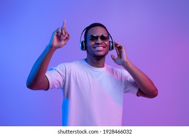 Happy African American Guy In Neon Light Listening Music In Wireless Headphones And Dancing, Cheerful Young Black Man Having Fun Over Purple Background, Enjoying His Favorite Songs, Copy Space