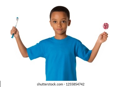 Happy african american little boy with toothbrush and sweet lolipop. Healthy teeth concept. Unhealthy food.