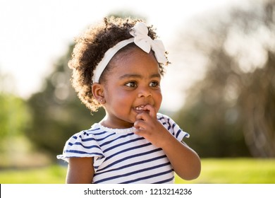 Happy African American little girl laughing and smiling outside.