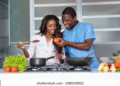 Happy african american love couple cooking at kitchen at home