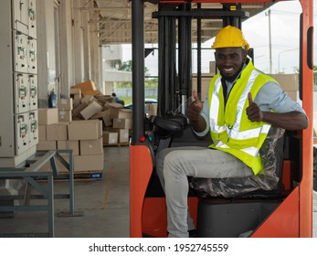 Happy African American male warehouse worker wearing  uniform suit and safety helmet drove a forklift truck to lift the goods to be arranged in warehouse in preparation for delivery to the customers