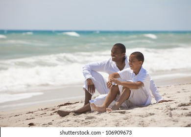 A happy African American man and boy, father and son, family together on a tropical beach in summer sunshine