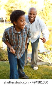 Happy African American man and boy, father and son, family together outside in the summer sunshine.