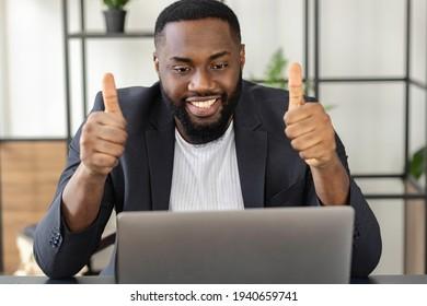 Happy Afroamerikaner, Freelancer oder Geschäftsmann, der den Laptop glücklich anschaut, eine gute Nachricht erhalten hat oder ein gutes Angebot gemacht hat