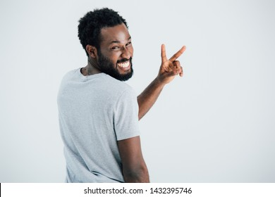 happy african american man in grey t-shirt showing victory sign isolated on grey