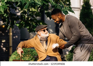 happy african american man helping senior disabled man to get up from wheelchair on street