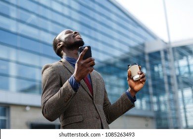Happy African American man looks lucky reading something in his smartphone while he stands outside with a cup of coffee