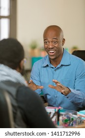 Happy African American man in an office talking with a client or coleague