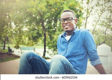 Happy African American man sitting and smiling in the park