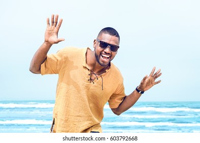Happy african american man with sun glasses big smile in flying gesture standing at beach in joyful attitude on blue sky ocean background - Cheerful black guy carefree and positive having fun outdoors