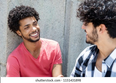 Happy african american man talking with friend outdoor in the city in the summer