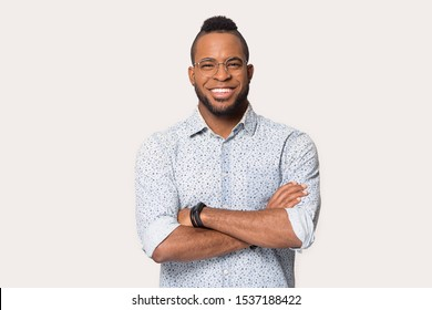 Happy african American man wearing shirt and glasses isolated on grey studio background stand posing with arms crossed, smiling biracial male in spectacles look at camera show white healthy teeth