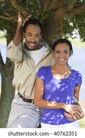 A happy African American man and woman couple standing outside under a tree and holding hands.