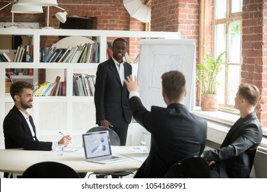 Happy african american manager presents business plan on flipchart, caucasian coworker rises hand to ask question about presentation, work team works on laptops with financial charts. Public speaking