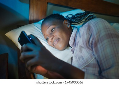 happy African American millennial woman as social media addict - night lifestyle portrait of young beautiful and cool black girl texting or online dating on mobile phone in bed smiling cheerful