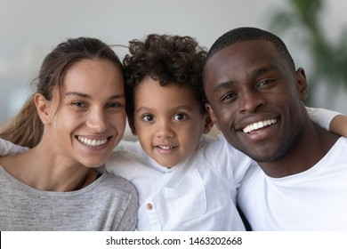 Happy african american mixed race ethnicity family with cute kid son bonding looking at camera at home, smiling black father caucasian mother and cute little child boy embracing, close up portrait