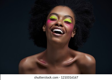 happy african american model with bright neon makeup posing isolated on black