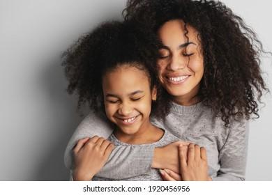 Frohe afrikanische amerikanische Mutter und ihre süße kleine Tochter lächeln und umarmen mit geschlossenen Augen.
