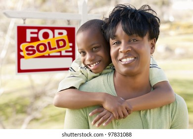Happy African American Mother and Child In Front of Sold Real Estate Sign.