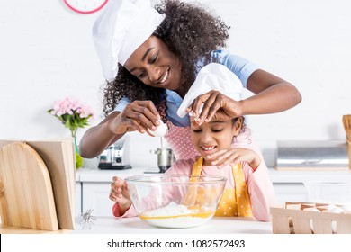 happy african american mother and daughter in chef hats making dough on kitchen