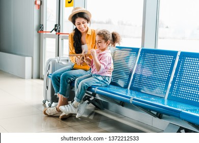 happy african american mother and daughter sitting in airport with suitcase and wooden plane model
