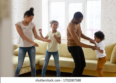 Happy african american mother and father with two children dancing. Diverse brother and sister with parents enjoying tender moment at living room.