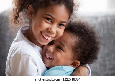 Happy African American siblings embracing, sitting together on couch at home in living room, little preschooler girl hug toddler adorable boy, good relations between sister and brother, close up