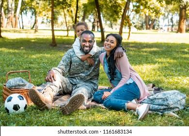 happy african american soldier sitting on grass with family in park