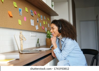 Happy african american teen girl student worker wear headphones video conference calling online on laptop computer laughing at home office. Elearning zoom app video call, distance videoconference.