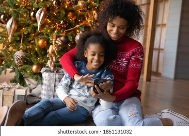 Happy African American woman with adorable little daughter using phone, looking on smartphone screen, shopping online, choosing gifts, sitting on warm floor near Christmas tree at home