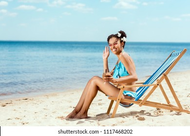 happy african american woman in bikini with cocktail in coconut shell waving by hand while sitting on deck chair on sandy beach