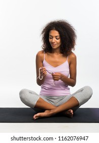Happy african american woman in comfortable sports wear meditating with mala rosary beads on mat over white wall background. Black girl concentrated on yoga practice.