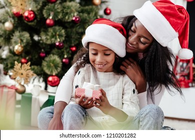 happy african american woman and daughter with gift in santa claus hats at home, newy year and christmas concept