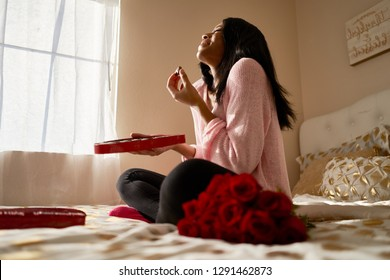 happy african american woman eating romantic valentines chocolates from heart shaped box while sitting on bed at home