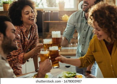 Happy African American woman and her friends having fun while toasting with beer in dining room.