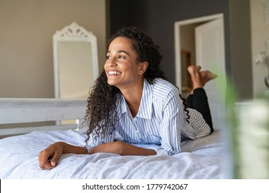 Happy african american woman lying on front and thinking. Thoughtful mixed race girl lying on bed while looking up in contemplation. Smiling young latin woman daydreaming while relaxing at home.