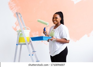 Happy African American woman painting wall in her new apartment. Renovation, redecoration and repair concept.