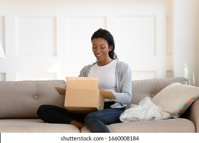 Happy African American woman sit on couch excited open cardboard box with online order, smiling biracial female rest on sofa at home do unpacking, purchase goods in Internet, good delivery concept