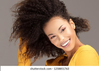 Happy african american woman smiling. Beautiful female half-length portrait. Young emotional afro woman. The human emotions, facial expression concept.
