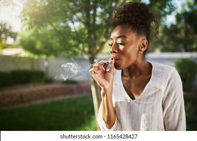 happy african american woman smoking marijuana joint in back yard