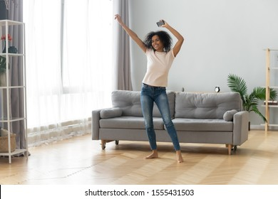 Happy African American woman using phone, listening to music on cellphone, smiling emotional girl holding mobile device, receive good news, dancing to favorite song at home, having fun alone