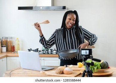 Happy african american woman vlogger broadcasting live video online teaching cooking food in kitchen at home