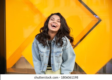 Happy African American woman wearing denim jacket laughing looking at camera standing near city street building. Smiling positive mixed race generation z hipster lady posing outdoor.