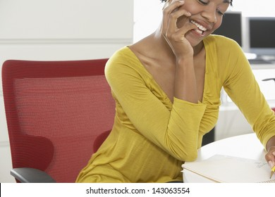 Happy African American woman writing on notepad at office desk