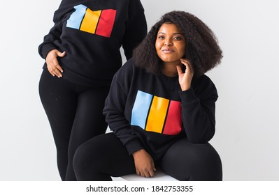Happy African American women have relationships, toothy smile, happy to meet with friends, dressed casually on white background. Emotions and friendship concept.