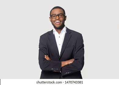 Happy african american young businessman in formal suit wearing eyeglasses portrait. Smiling millennial confident black guy posing for photo, looking at camera, isolated on grey studio background.